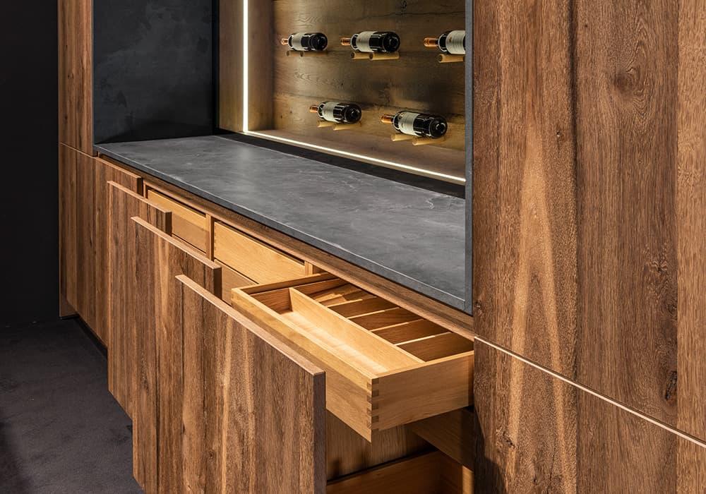 Abbildung Massivholzküche von BAX mit geöffneten Schränken und Schubladen sowie beleuchtetem Weinregal an der Wand